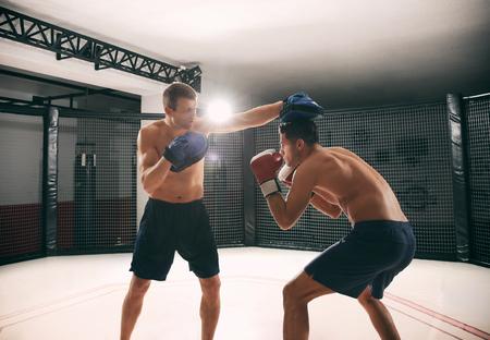 Foto de Young boxer training in gym with personal coach - Imagen libre de derechos