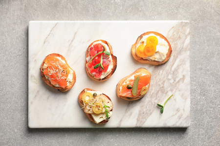Photo pour Marble board with tasty fresh bruschettas on table - image libre de droit