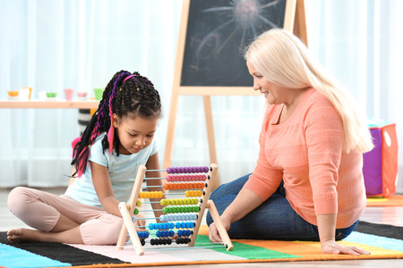 Photo pour Female mature nanny teaching little African-American girl to count using abacus - image libre de droit