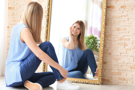 Photo pour Young woman looking at herself in mirror indoors - image libre de droit
