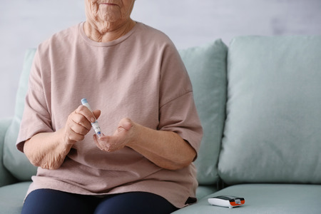 Photo pour Elderly woman with diabetes measuring level of blood sugar at home - image libre de droit