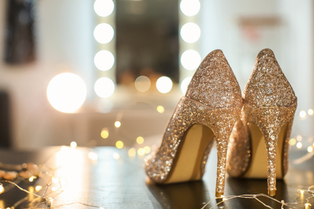 Photo pour Beautiful high heeled shoes on table with fairy lights - image libre de droit