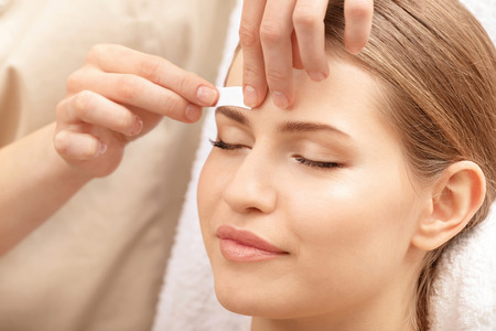 Photo for Young woman undergoing eyebrow correction procedure in salon - Royalty Free Image