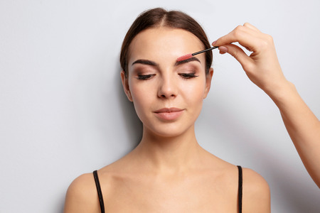 Foto per Young woman undergoing eyebrow correction procedure on light background - Immagine Royalty Free