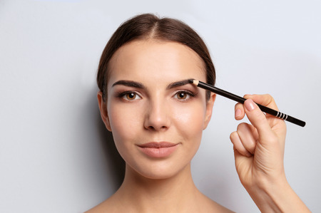 Foto de Young woman undergoing eyebrow correction procedure on light background - Imagen libre de derechos