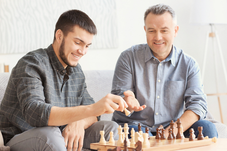Photo pour Mature man playing chess with his son at home - image libre de droit