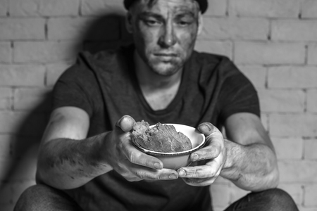 Photo for Hungry poor man holding bowl with piece of bread while sitting near brick wall - Royalty Free Image