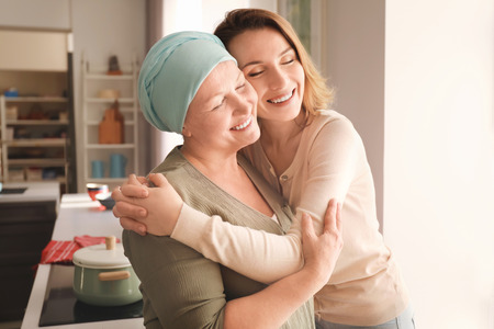 Photo for Young woman visiting her mother with cancer indoors - Royalty Free Image