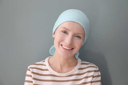 Photo pour Young woman with cancer in headscarf on grey background - image libre de droit