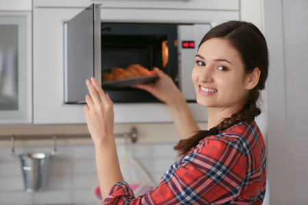 Photo pour Woman putting plate with pastry in microwave indoors - image libre de droit