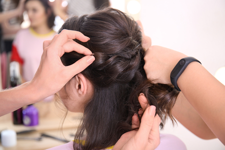 Photo pour Professional hairdresser and trainee working with client in salon. Apprenticeship concept - image libre de droit