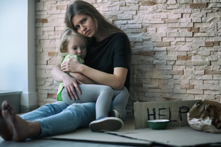 Photo pour Homeless poor woman and her little daughter sitting near brick wall and asking for help - image libre de droit