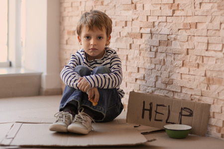 Foto de Homeless poor boy with empty bowl and carton board with word HELP sitting near brick wall - Imagen libre de derechos