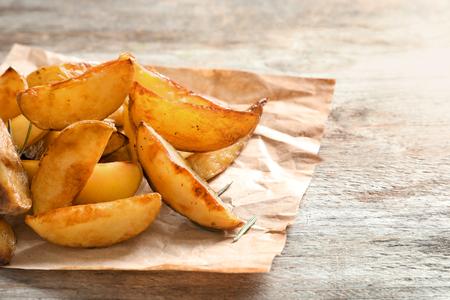 Photo pour Delicious baked potato wedges on wooden background - image libre de droit
