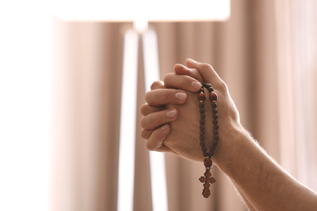 Photo pour Hands of religious young man with rosary beads praying at home - image libre de droit