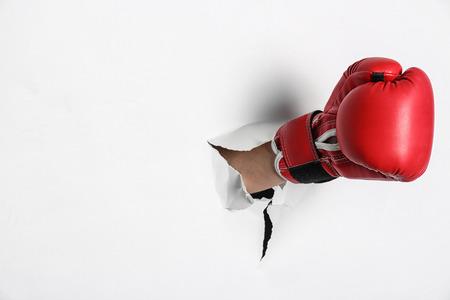 Photo pour Man in boxing glove breaking through white paper - image libre de droit