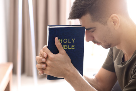 Photo for Religious young man with Bible praying at home - Royalty Free Image