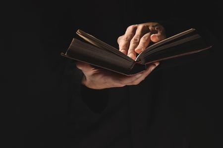 Photo pour Priest with old Bible on black background, closeup - image libre de droit