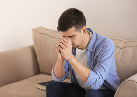 Photo for Religious young man praying to God at home - Royalty Free Image