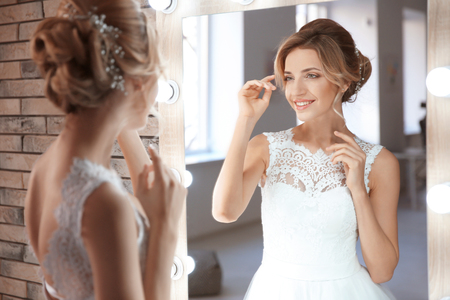 Foto de Beautiful young bride in white wedding dress with makeup created by professional artist near mirror indoors - Imagen libre de derechos
