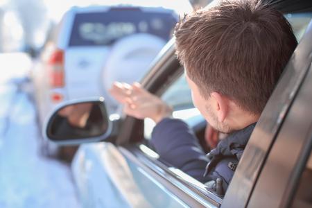 Photo pour Emotional young man inside car in traffic jam - image libre de droit