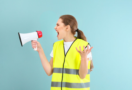 Foto per Young woman in reflective vest shouting into megaphone on color background - Immagine Royalty Free