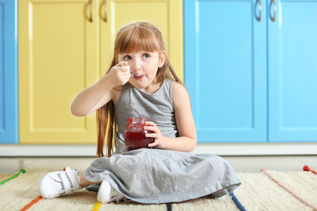 Photo pour Cute little girl eating jam at home - image libre de droit