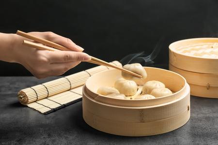 Foto de Woman with tasty baozi dumplings in bamboo steamer on table - Imagen libre de derechos
