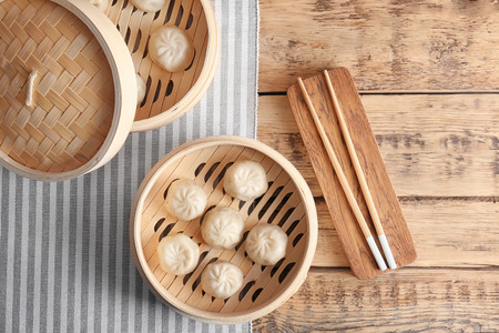 Foto de Bamboo steamers with tasty baozi dumplings on table - Imagen libre de derechos