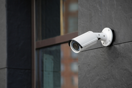 Photo pour Modern CCTV camera on wall of building outdoors - image libre de droit