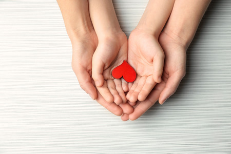 Photo pour Hands of mother and child with small red heart on light background - image libre de droit