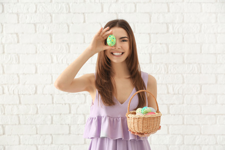 Photo pour Beautiful young woman with basket full of colorful Easter eggs against white brick wall - image libre de droit