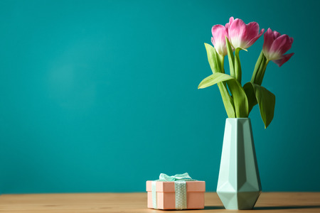 Photo pour Vase with beautiful tulips and gift box on table against color background - image libre de droit