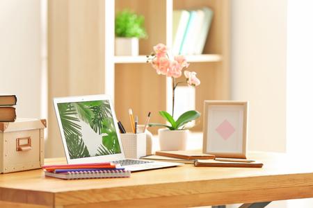 Photo pour Comfortable home workplace with laptop on table - image libre de droit
