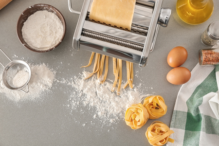 Photo for Metal pasta maker with dough on kitchen table, top view - Royalty Free Image