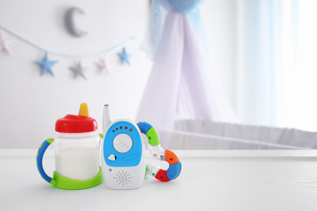 Foto de Baby monitor, rattle and sippy cup on table in room. Radio nanny - Imagen libre de derechos
