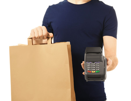 Foto de Delivery man holding paper bag with food and payment terminal on white background - Imagen libre de derechos