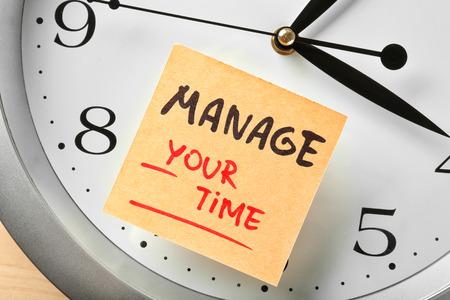 Photo pour Clock and sticker paper with phrase MANAGE YOUR TIME, closeup - image libre de droit