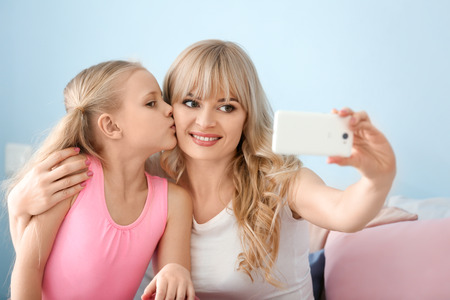 Foto de Cute little girl and her mother taking selfie at home - Imagen libre de derechos