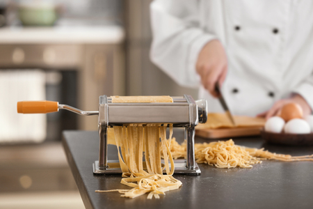 Photo for Pasta maker with dough and blurred chef on background - Royalty Free Image