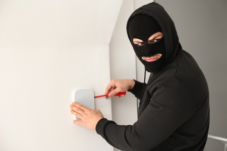 Male thief trying to break alarm system, indoors