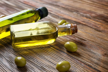 Photo for Bottles with olive oil on wooden table - Royalty Free Image