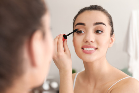 Foto de Young beautiful woman applying makeup in morning - Imagen libre de derechos
