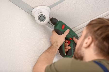Foto de Electrician installing security camera indoors - Imagen libre de derechos