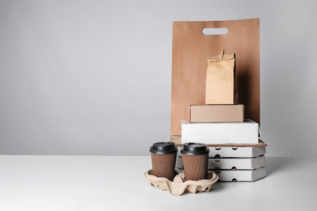 Photo pour Different packages and carton cups on table against color background. Food delivery service - image libre de droit