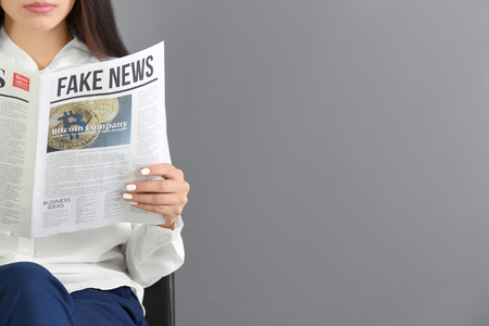 Photo for Young woman reading newspaper against grey background - Royalty Free Image