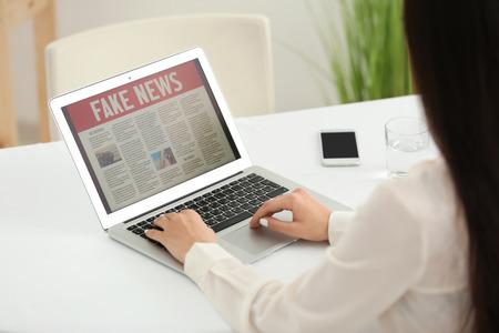 Foto de Young woman reading news on laptop screen indoors - Imagen libre de derechos