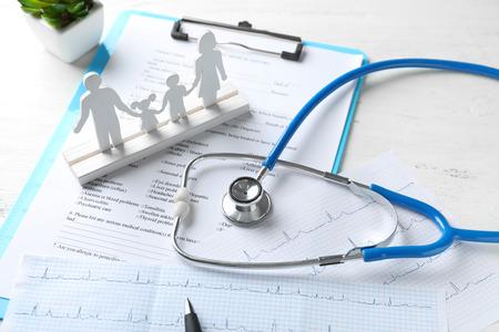 Foto de Composition with family figure and stethoscope on wooden table. Health care concept - Imagen libre de derechos