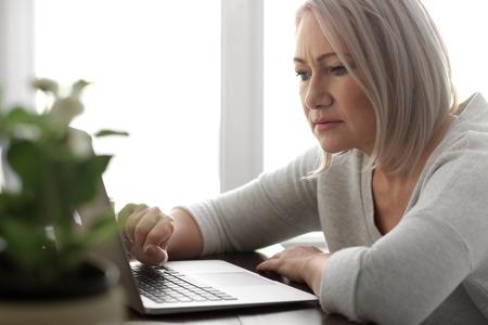 Photo pour Mature woman reading news on laptop screen in cafe - image libre de droit