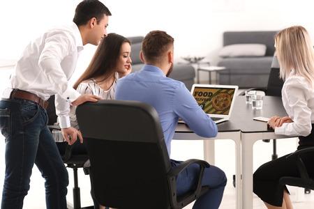 Foto de Young people using laptop for ordering food in office - Imagen libre de derechos